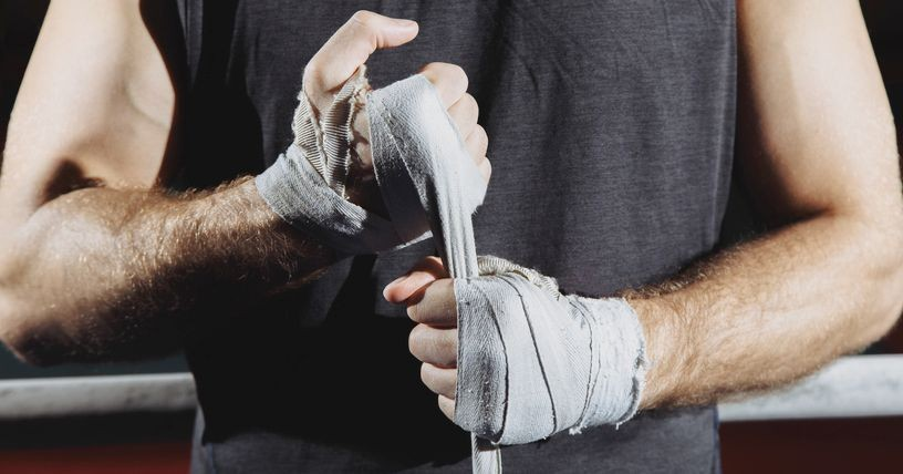 Strong man wrap hands on black background. Man is wrapping hands with boxing wraps, ready for training and active exercise
