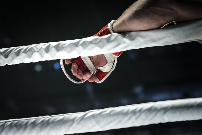 closeup hand of fighter MMA in glove lays ropes of ring